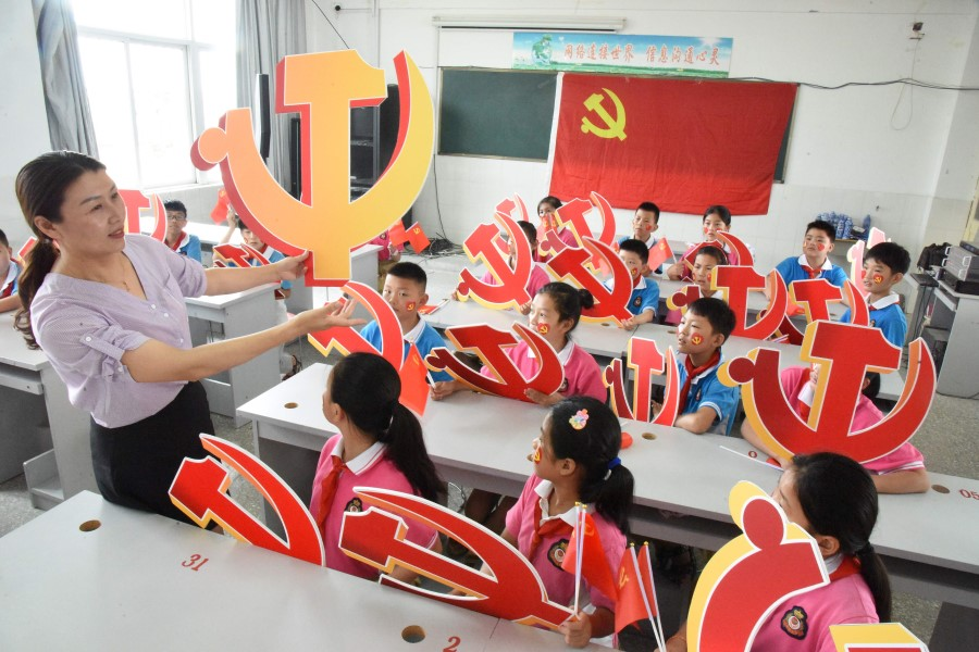 In this file photo a teacher and her students pose with Communist Party emblems during a class about the history of the Communist Party at a school in Lianyungang, in China's eastern Jiangsu province, 28 June 2020. (STR/AFP)