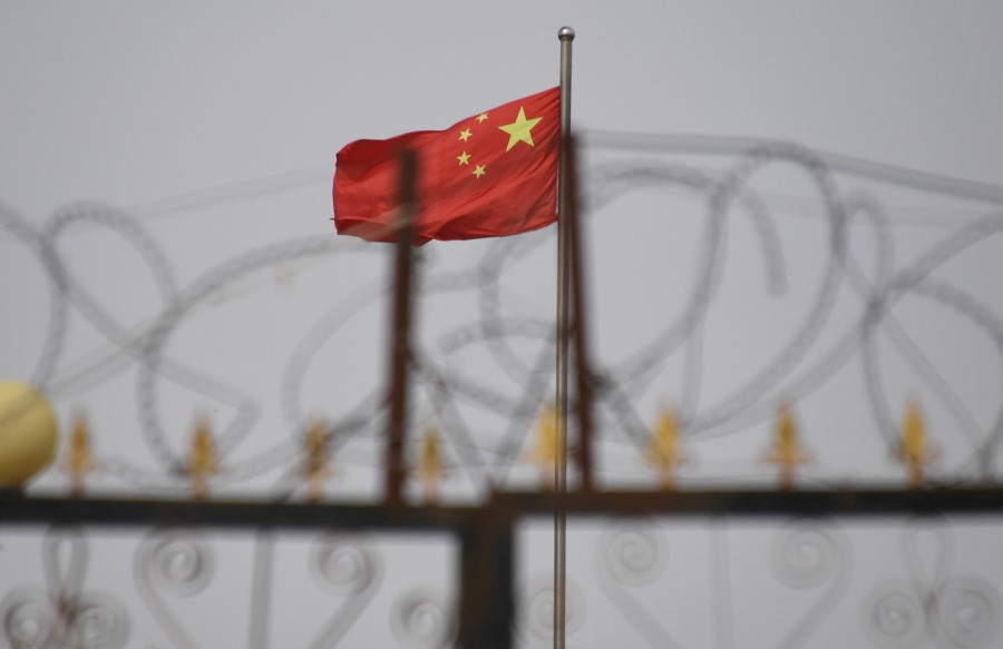 This file photo taken on 4 June 2019 shows the Chinese flag behind razor wire at a housing compound in Yangisar, south of Kashgar, in China's western Xinjiang region. - The US will seize all imports of tomato and cotton products from China's Xinjiang region due to the use of forced labor, the Customs and Border protection agency announced on 13 January 2021. (Greg Baker/AFP)
