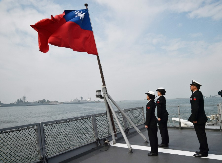 In this file photo taken on 31 January 2018, Taiwanese sailors salute the island's flag on the deck of the Panshih supply ship after taking part in annual drills, at the Tsoying naval base in Kaohsiung. (Mandy Cheng/AFP)