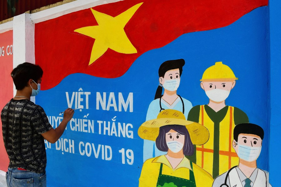 In this file photo, a street artist paints a mural depicting Covid-19 coronavirus frontline workers along a street in Hanoi on 15 June 2021. (Nhac Nguyen/AFP)