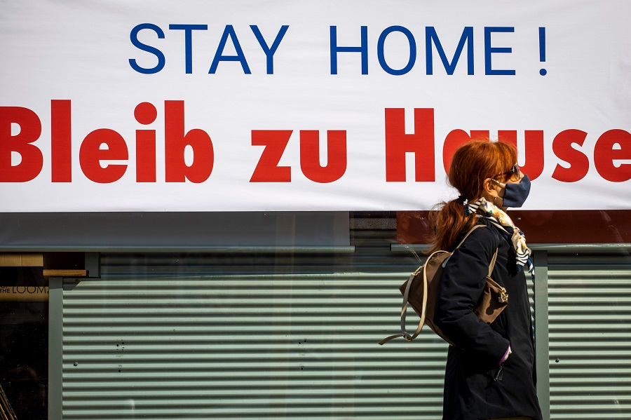 In this photo taken on 28 March 2020, a shopper walks past a print shop in Berlin with a sign advising its customers to stay at home amid the novel coronavirus pandemic. (Odd Andersen/AFP)