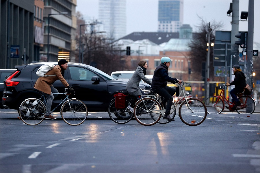 Bicycle and car commuters are seen crossing a busy intersection at Potsdamer Platz in Berlin, Germany, on 7 December 2020. (Odd Andersen/AFP)