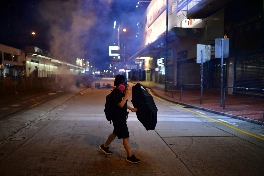 Night falls as a lone protester walks on the street. (Anthony Wallace/AFP)