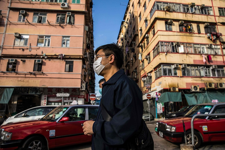 In this picture taken on 29 February 2020, people wearing face masks as a precautionary measure against the spread of the Covid-19 coronavirus walk past residential buildings in Hong Kong. (Dale De La Rey/AFP)