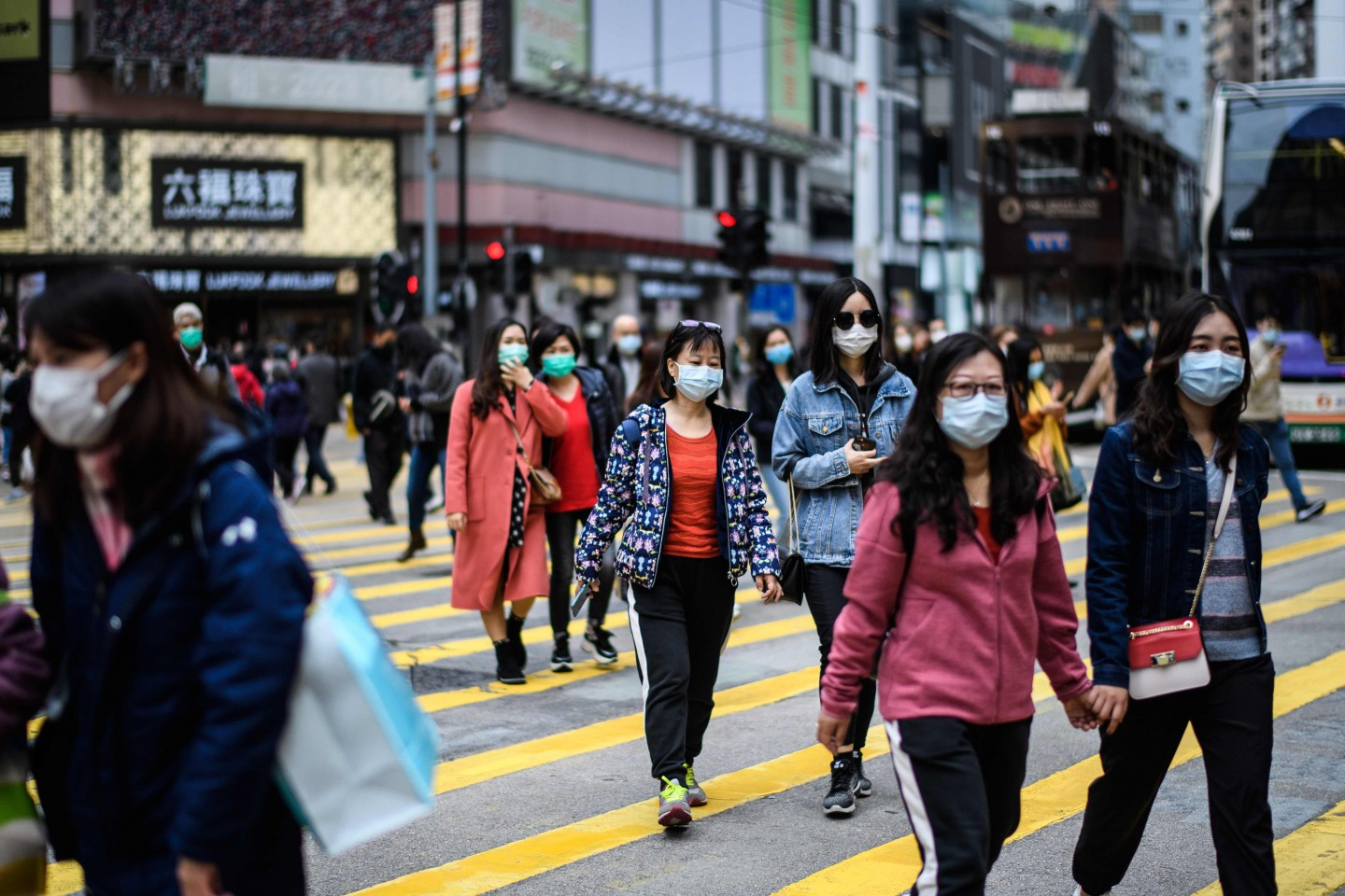 The scale of the Wuhan coronavirus outbreak triggered frightening memories of the 2003 SARS epidemic. In this photo taken in Hong Kong on 27 January 2020, pedestrians are seen wearing face masks while crossing the road as a preventative measure following the Wuhan coronavirus outbreak. (Anthony Wallace/AFP)