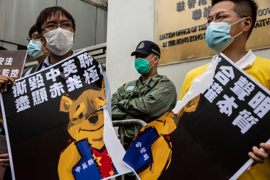 Pro-democracy activists tear a placard of Winnie-the-Pooh that represents Chinese President Xi Jinping during a protest against a proposed new security law outside the Chinese Liaison Office in Hong Kong, 24 May 2020. (Isaac Lawrence/AFP)
