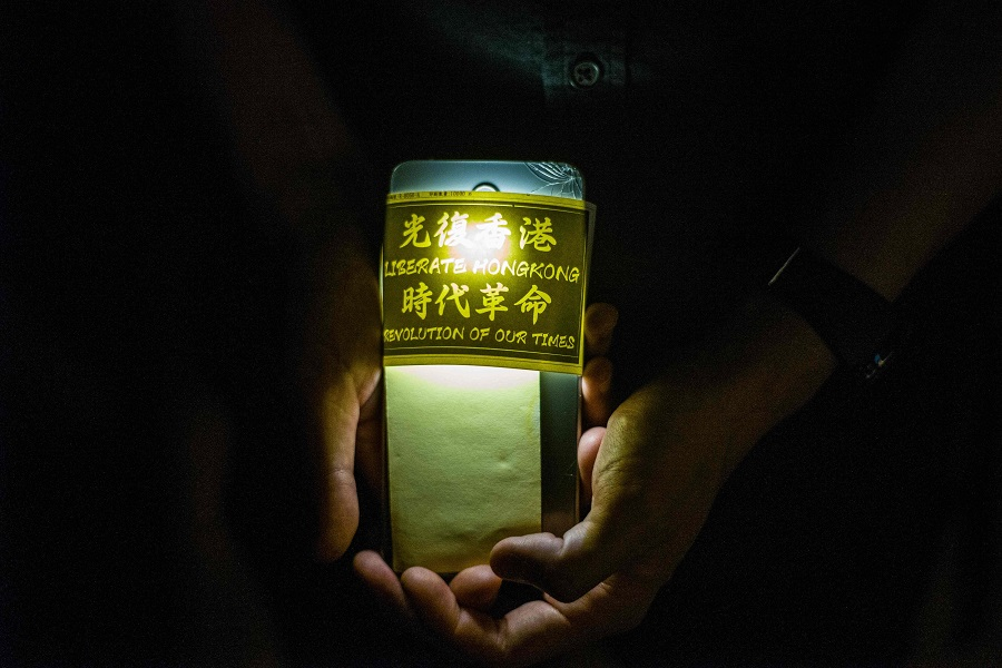 A pro-democracy activist holds his phone while queueing to pay respects to mark the one year anniversary of a man who fell to his death after hanging a protest banner against the now-withdrawn extradition bill on the scaffolding outside a shopping mall, in Hong Kong on 15 June 2020. (Anthony Wallace/AFP)