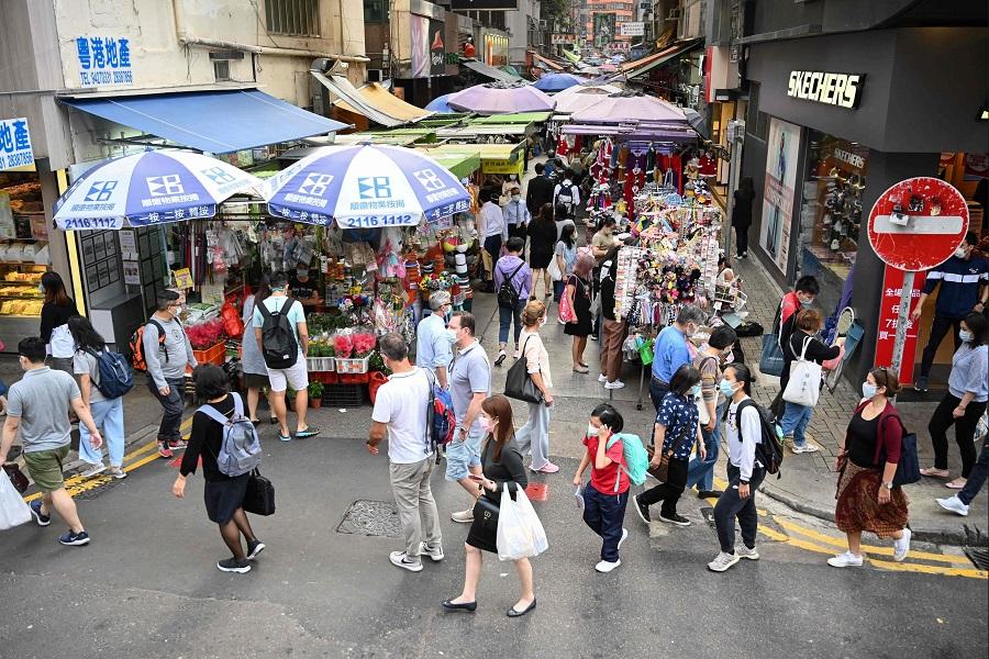 Pedestrians walk past market stalls along a street inHongKongon 24 November 2020. (Peter Parks/AFP)