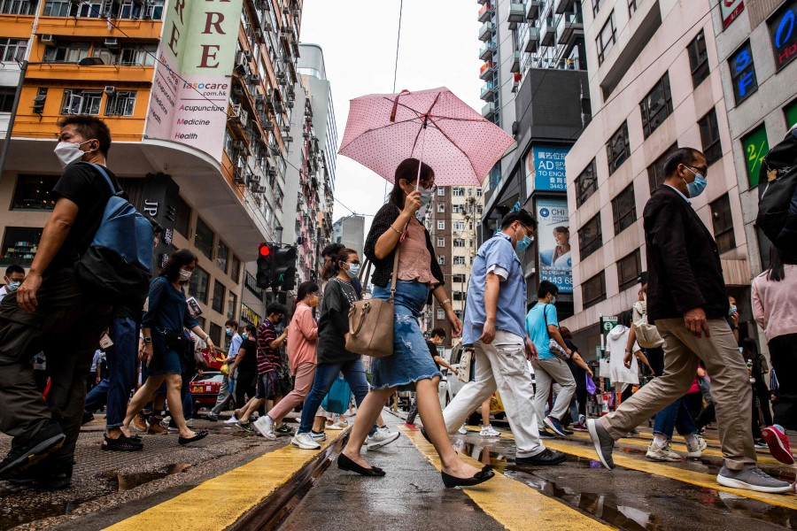 Pedestrians walk on a street in the Wanchai district of Hong Kong on 6 August 2021. (Isaac Lawrence/AFP)