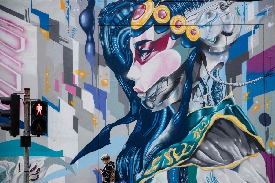 "A pedestrian walks past a mural from the ""Heart of Cyberpunk"" exhibition in Sham Shui Po district in Hong Kong on 24 October 2020. (Photo by May JAMES / May James / AFP)"