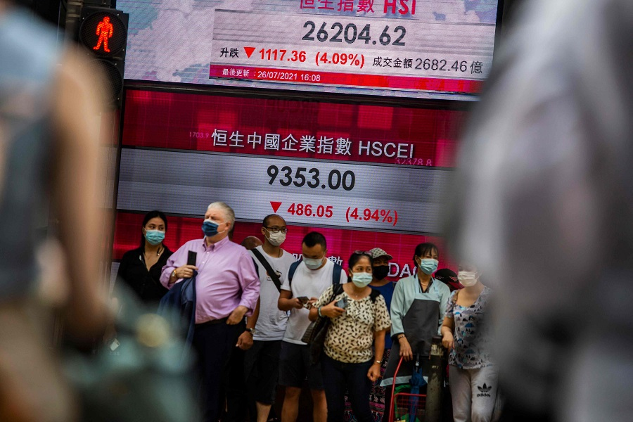 People stand in front of an electronic display showing the Hang Seng Index in the Central district of Hong Kong on 26 July 2021. (Isaac Lawrence/AFP)