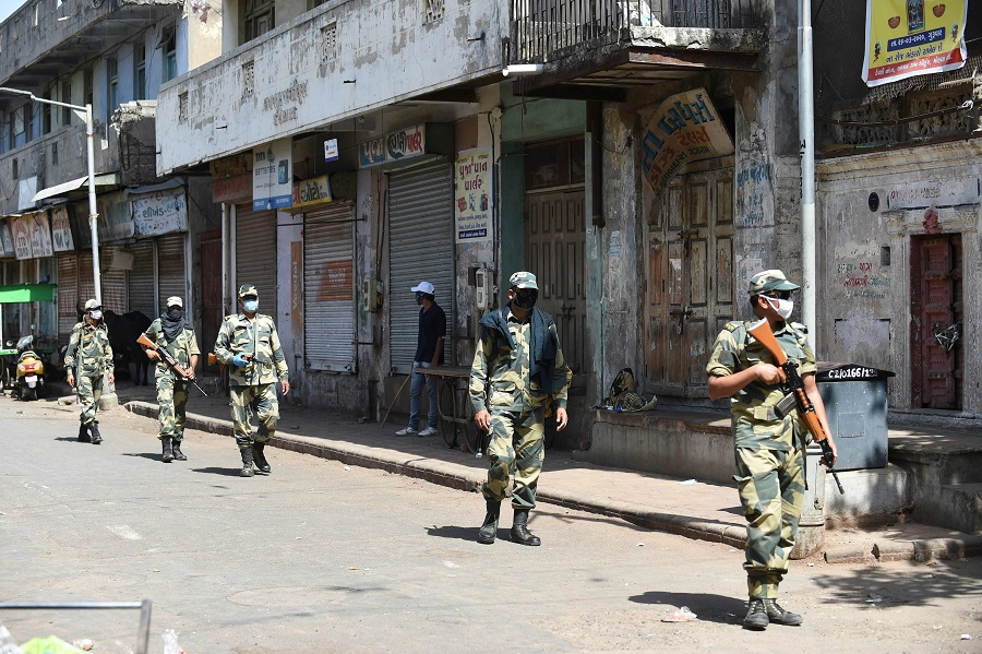 Paramilitary soldiers from the Border Security Force patrol a street during a government-imposed nationwide lockdown as a preventive measure against the Covid-19 coronavirus, in Ahmedabad, India, on 8 May 2020. (Sam Panthaky/AFP)
