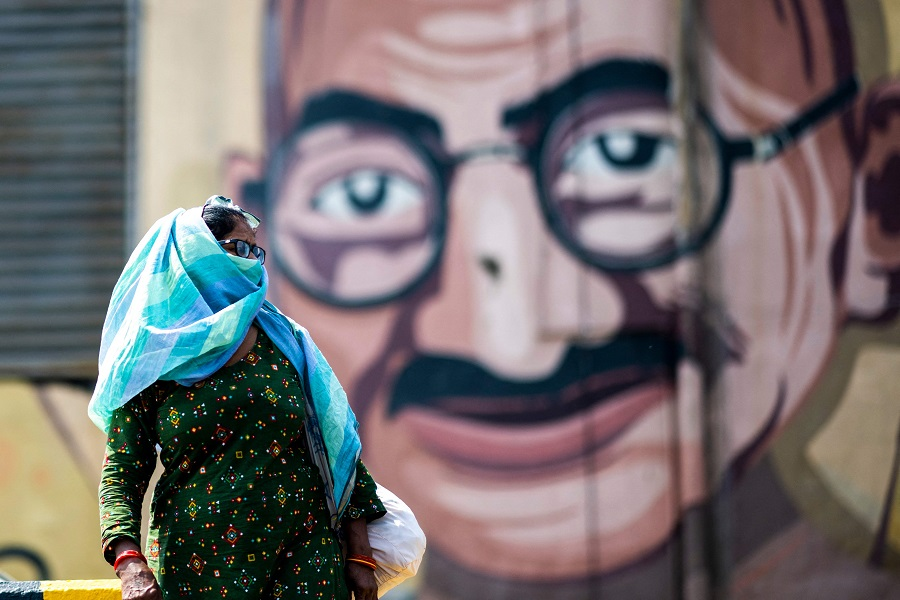 A woman crossing a street passes by a wall art depicting Indian independence hero Mahatma Gandhi during a government-imposed lockdown to prevent the Covid-19 coronavirus from spreading in Noida, India on 21 May 2021. (Jewel Samad/AFP)