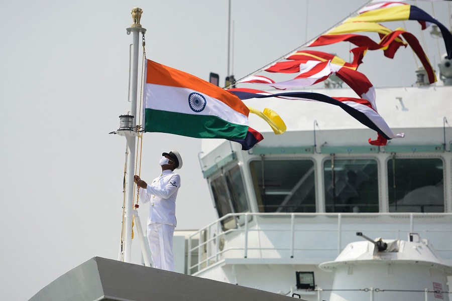 """A coast guard official raises the Indian national flag on board the Indian Coast Guard offshore patrol vessel """"Vajra"""" during its commissioning ceremony, in Chennai, India, on 24 March 2021. (Arun Sankar/AFP)"""