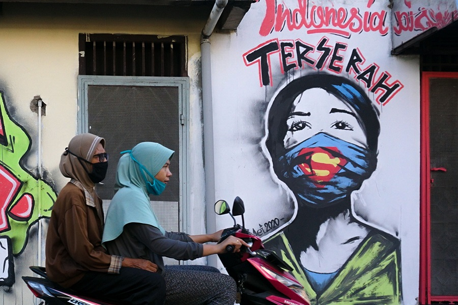 """Two girls wearing face masks ride a scooter past a mural reading """"whatever Indonesia"""" in Tangerang on 23 May 2020. (Fajrin Raharjo/AFP)"""