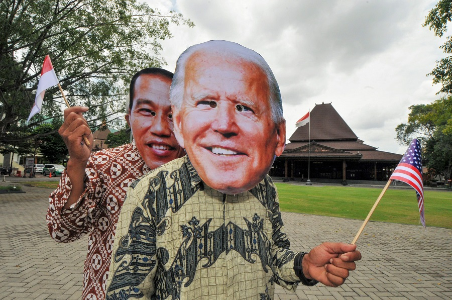 People wearing masks depicting the faces of Indonesian President Joko Widodo (left) and US President Joe Biden (right) pose in Surakarta, Central Java, Indonesia, on 20 January 2020, ahead of Biden's presidential inauguration later in the day. (Anwar Mustafa/AFP)