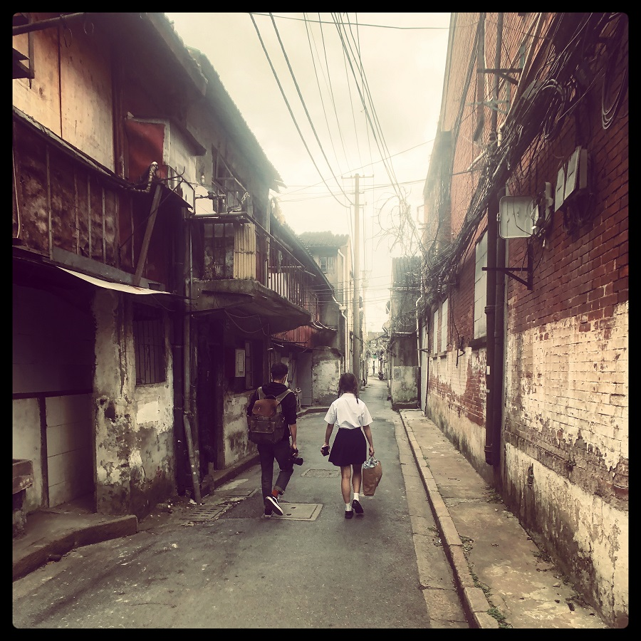 Boy and schoolgirl walk through a boarded-up neighbourhood in Laoximen.