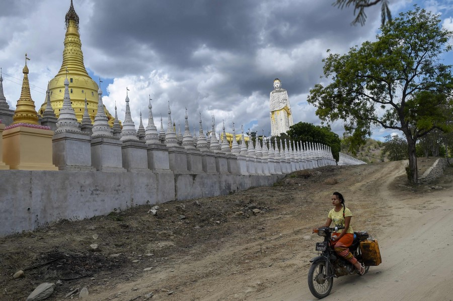 This photo taken on 25 July 2020 shows a girl riding a bike next to Buddhist pagodas in Monywa in the Sagaing region in Myanmar. (Ye Aung Thu/AFP)