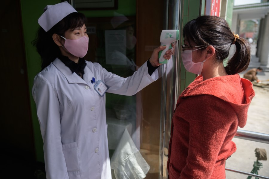 A health worker takes the temperature of a woman amid concerns over the Covid-19 coronavirus, at an entrance of the Pyongchon District People's Hospital in Pyongyang, 1 April 2020. (Kim Won Jin/AFP)