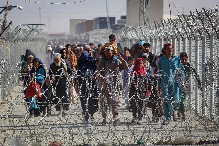 Afghans walk along fences as they arrive in Pakistan through the Pakistan-Afghanistan border crossing point in Chaman on 24 August 2021 following Taliban's military takeover of Afghanistan. (AFP)