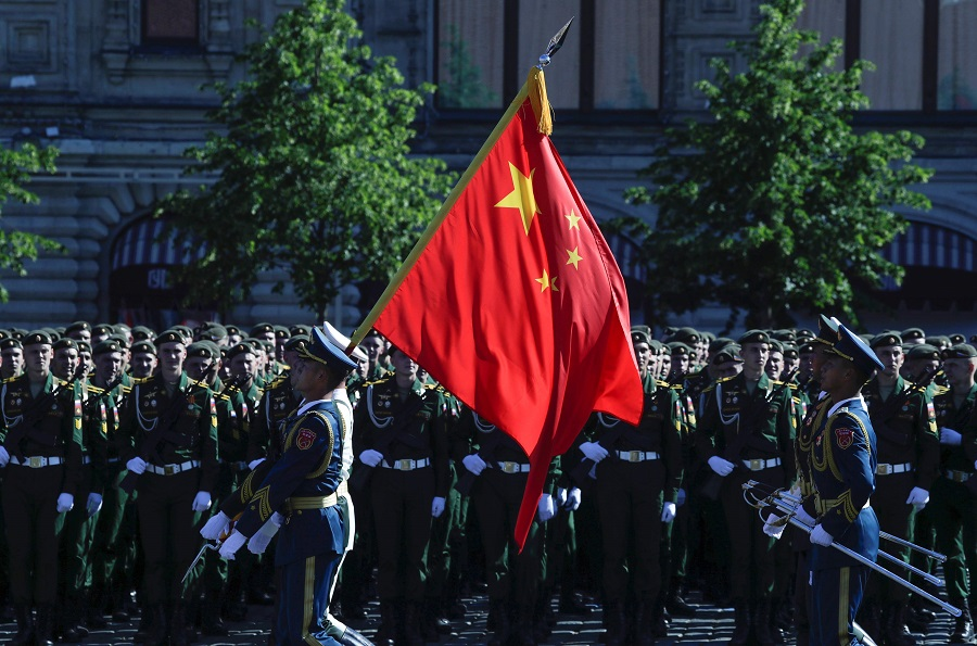 Soldiers from China's People's Liberation Army carry a state flag at Red Square prior to a military parade, which marks the 75th anniversary of the Soviet victory over Nazi Germany in World War II, in Moscow on 24 June 2020. (Pavel Golovkin/POOL/AFP)