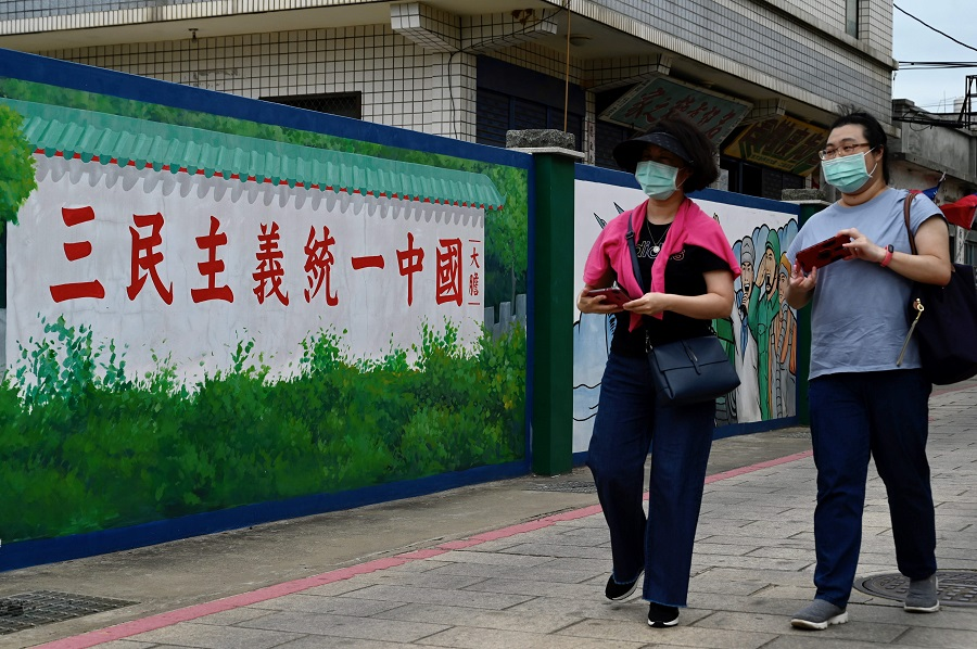 """This photo taken on 21 October 2020 shows tourists passing a wall with a slogan that says """"Grand Alliance for China's Reunification under the Three Principles of the People"""", on Taiwan's Kinmen islands. (Sam Yeh/AFP)"""