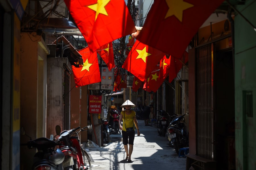 A woman walks along along an alleyway decorated with Vietnamese national flags in Hanoi, 1 September 2020. (Nhac Nguyen/AFP)