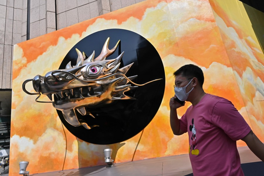 A man wearing a face mask walks past a dragon head decoration outside a mall in Bangkok on 21 January 2021. (Romeo Gacad/AFP)