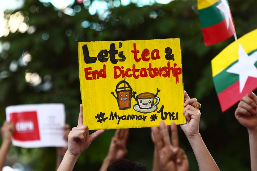 """Myanmar migrants in Thailand holds signs relating to the """"Milk Tea Alliance"""" as they take part in a protest in Bangkok on 28 February 2021, against the military coup in their home country. (Jack Taylor/AFP)"""