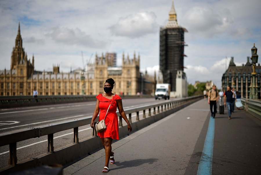 A pedestrian wearing a face mask walks over Westminster Bridge near the Houses of Parliament in central London on 7 June 2021. (Tolga Akmen/AFP)