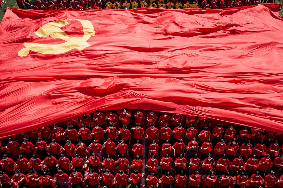 University students display a flag of the Communist Party of China to mark the party's 100th anniversary during an opening ceremony of the new semester in Wuhan, Hubei province, China, on 10 September 2021. (STR/AFP)