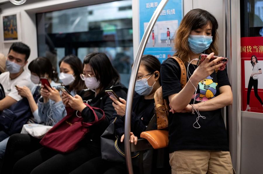 Passengers use their mobile phones on the subway in Beijing, 12 May 2020. (Noel Celis/AFP)