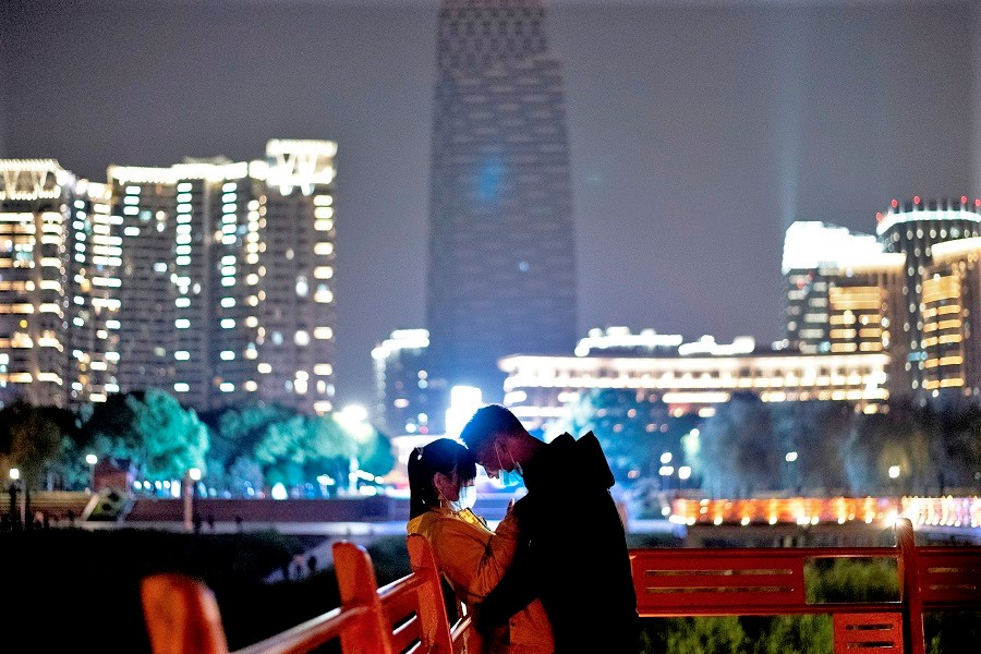 A couple wearing face masks cuddles along a park at the Yangtze river in Wuhan, Hubei, on 12 April 2020. (Noel Celis/AFP)