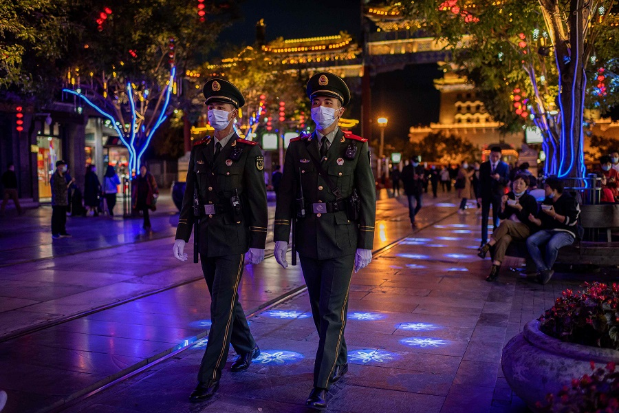 Paramilitary police officers wearing face masks patrol on a street in Beijing on 13 October 2020. (Nicolas Asfouri/AFP)