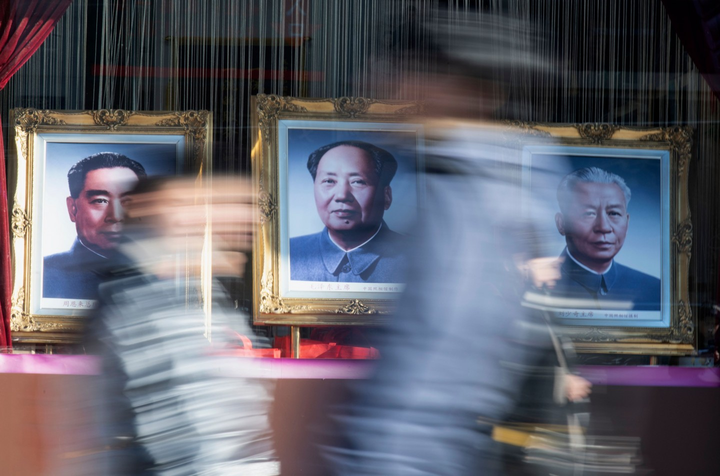 Is there life after death? In this photo, people walk past a picture of Mao Zedong in Beijing on 14 December 2019. (Noel Celis/AFP)