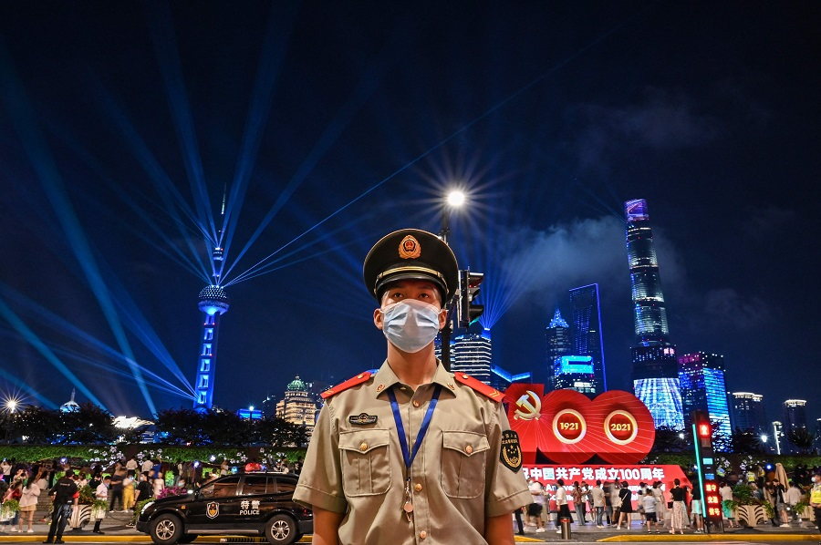 A Chinese paramilitary police stands guard while a light show is seen from the Bund in Shanghai on 30 June 2021, on the eve of the 100th anniversary of the Chinese Communist Party. (Hector Retamal/AFP)