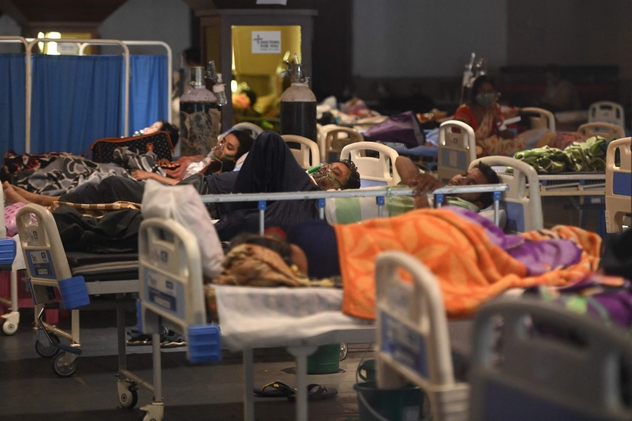 Patients breathe with the help of oxygen masks inside a banquet hall temporarily converted into a Covid-19 coronavirus ward in New Delhi on 27 April 2021. (Money Sharma/AFP)
