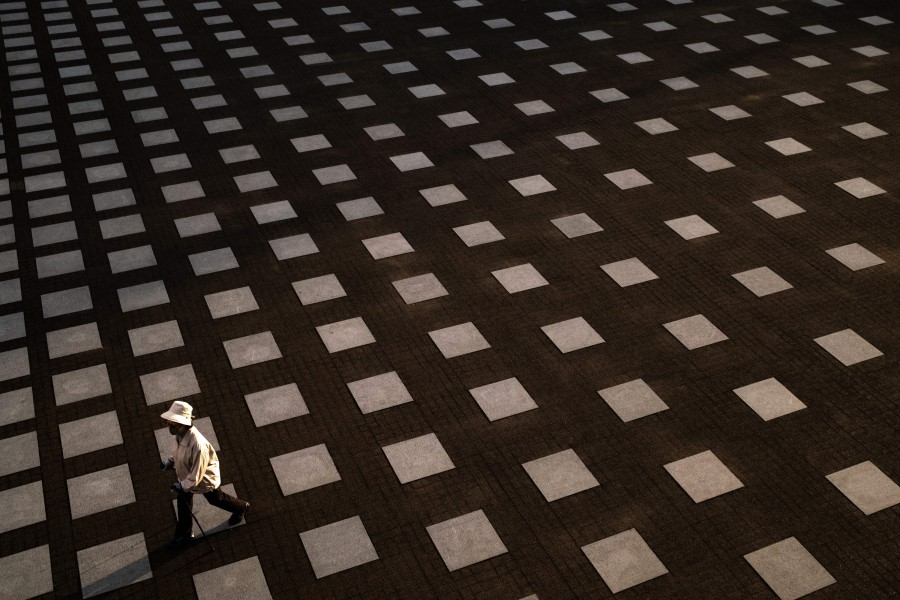 A woman wearing a face mask walks at a square of a park in Yokohama, 10 May 2020. (Philip Fong/AFP)