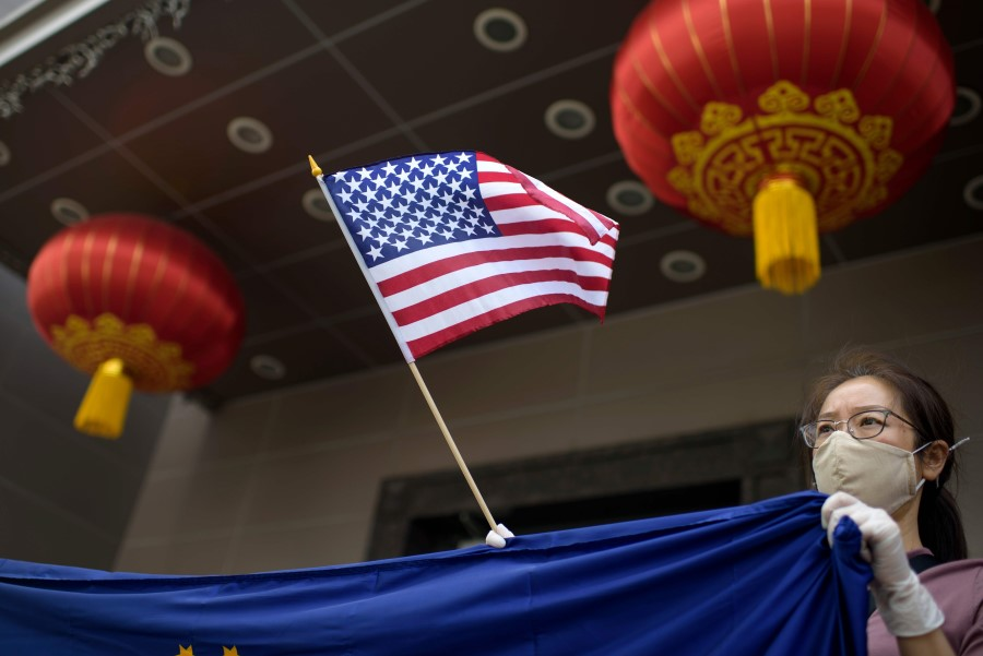 A protester holds a US flag outside of the Chinese consulate in Houston on 24 July 2020, after the US State Department ordered China to close the consulate. (Mark Felix/AFP)