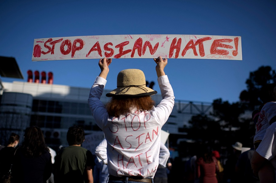 "A person holds up a sign during a ""Stop Asian Hate"" rally at Discovery Green in Houston, Texas, US, on 20 March 2021. (Mark Felix/AFP)"