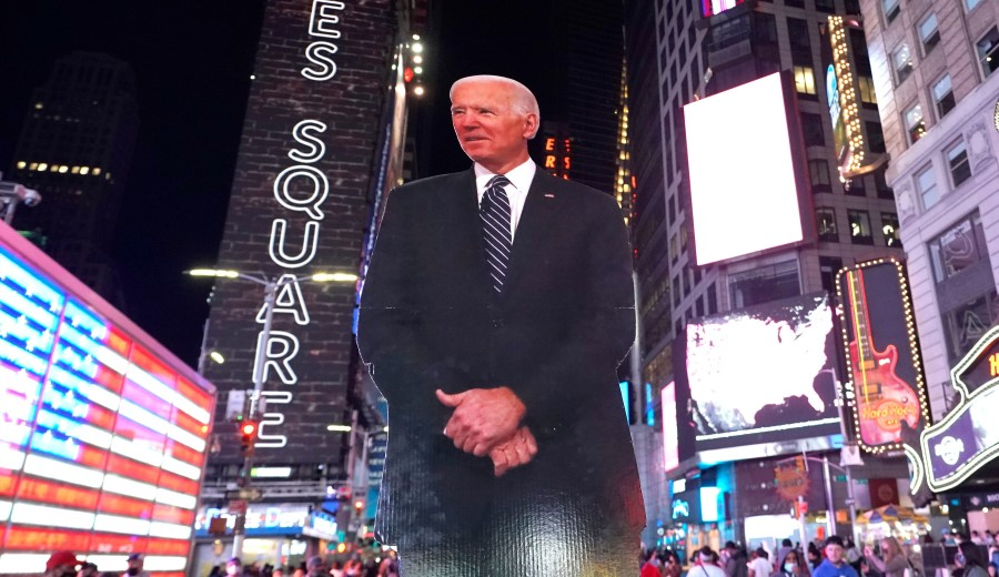People celebrate at Times Square in New York after Joe Biden was declared winner of the 2020 presidential election on 7 November 2020. (Timothy A. Clary/AFP)