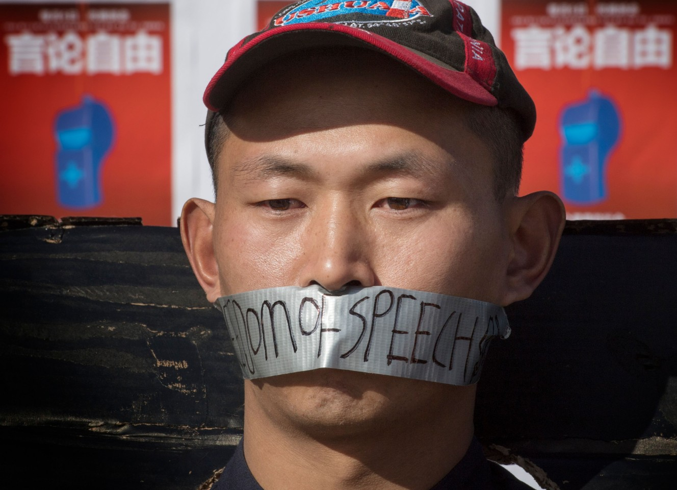 "Chinese students hold a memorial for Dr Li Wenliang outside the UCLA campus in Westwood, California, on 15 February 2020. In the photo, the student has the words ""freedom of speech"" written on the duct tape over his mouth. (Mark Ralston/AFP)"