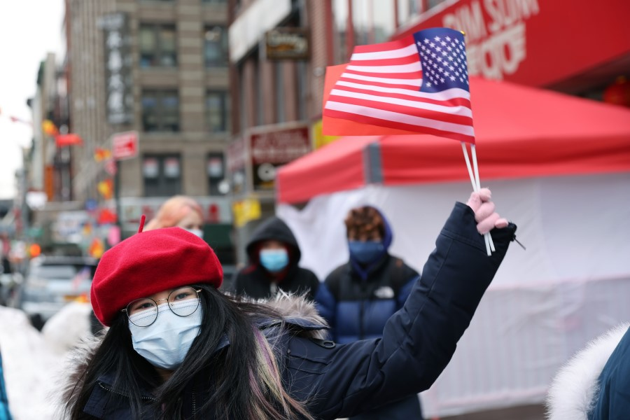 A woman holds the US and China flags at a Lunar New Year ceremony in Chinatown on 12 February 2021 in New York City. (Spencer Platt/AFP)