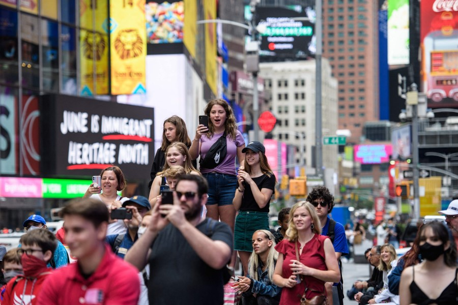 People watch a pop up event in Times Square on 11 June 2021 in New York City. (Angela Weiss/AFP)