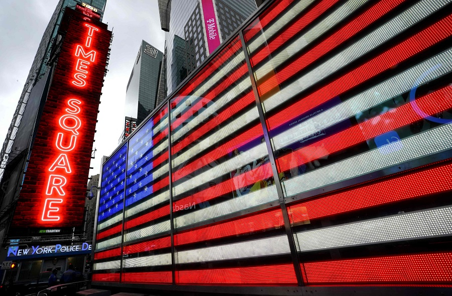 A neon sign of the American flag and neon lights at One Times Square in New York, 31 July 2020. (Timothy A. Clary/AFP)