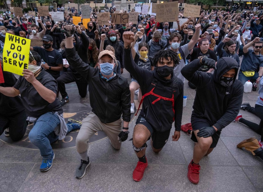 Protesters kneel and raise their arms as they gather peacefully to protest the death of George Floyd at the State Capital building in downtown Columbus, Ohio, 1 June 2020. (Seth Herald/AFP)