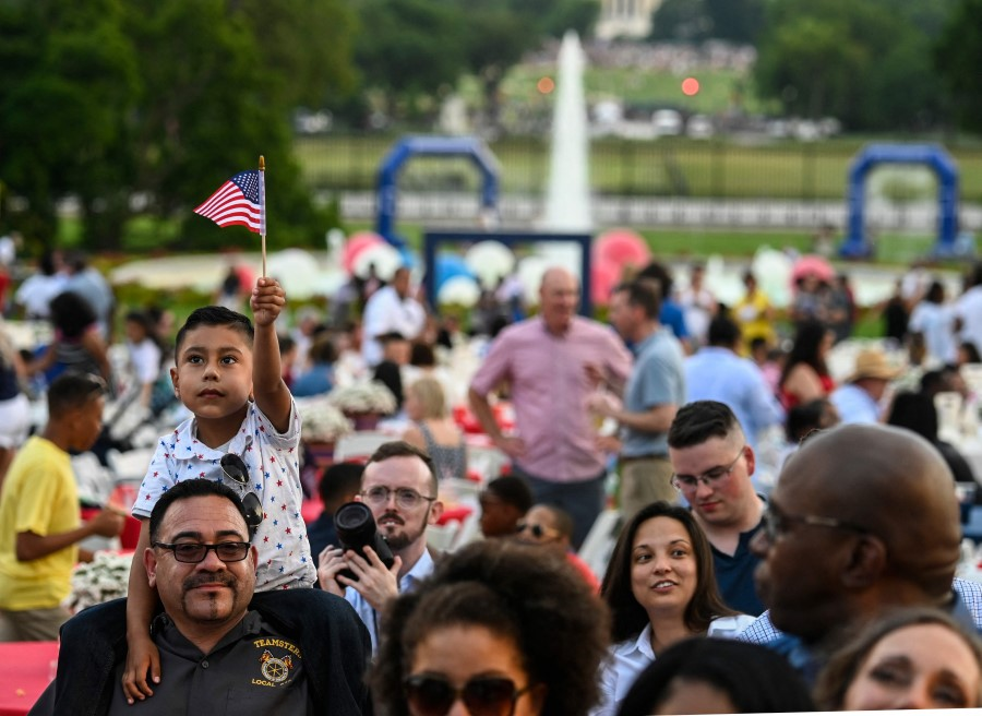 A boy holds up a US flag as guests attend Independence Day celebrations at the White House in Washington, DC, 4 July 2021. (Andrew Caballero-Reynolds/AFP)