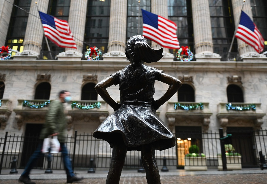 People walk past the New York Stock exchange (NYSE) and the 'Fearless Girl' statue at Wall Street after heavy rainfall on 30 November 2020 in New York City, US. (Angela Weiss/AFP)