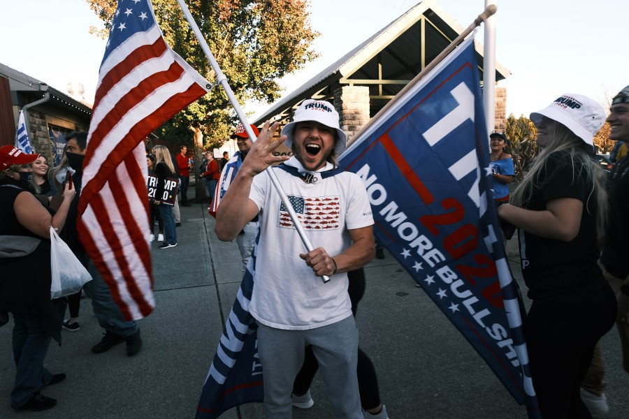 Supporters of President Donald Trump wave flags and hold signs at Skylands Stadium during an election rally on 14 October 2020 in Augusta, New Jersey. (Spencer Platt/AFP)