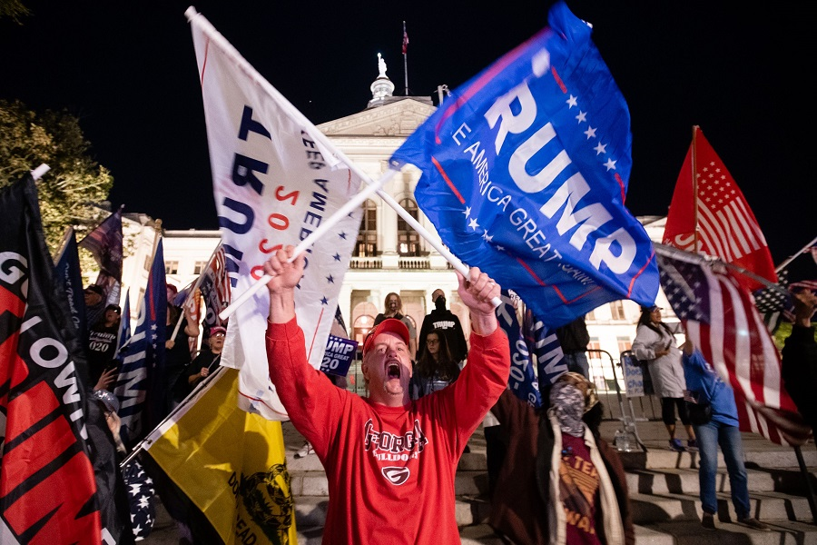 A supporter of President Donald Trump yells at counter-protesters across the street during a rally to protest against the election results outside the Georgia State Capitol on 14 November 2020 in Atlanta, Georgia. (Elijah Nouvelage/Getty Images/AFP)